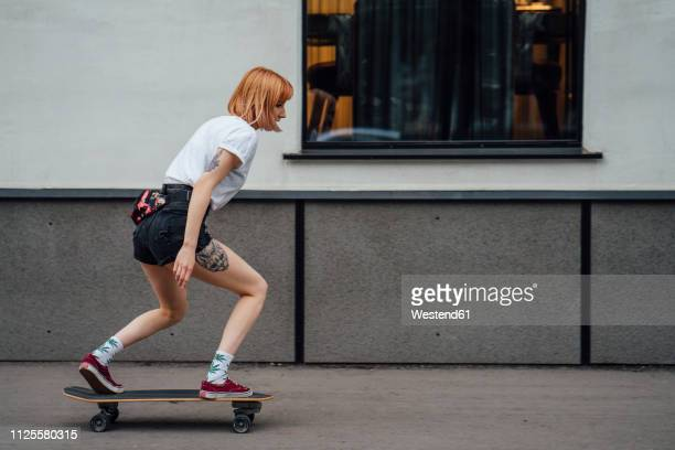 young woman riding carver skateboard on the sidewalk - skating stock pictures, royalty-free photos & images