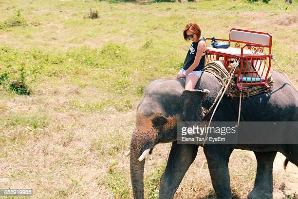 Young Woman Riding Elephant At Park
