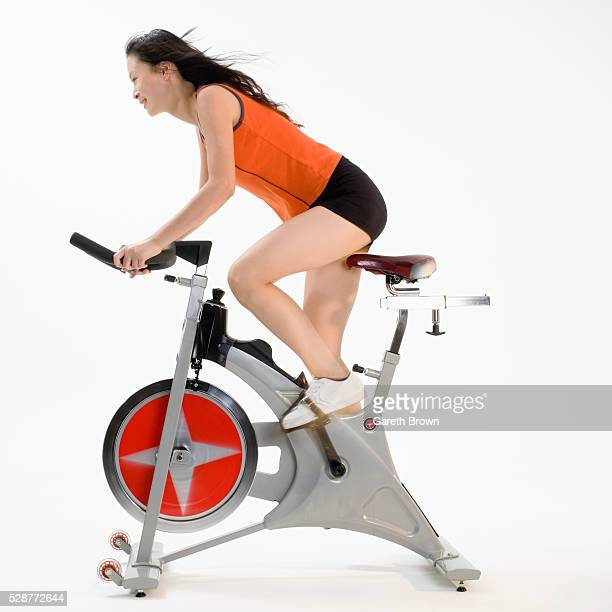 young woman riding exercise bicycle - peloton stock pictures, royalty-free photos & images