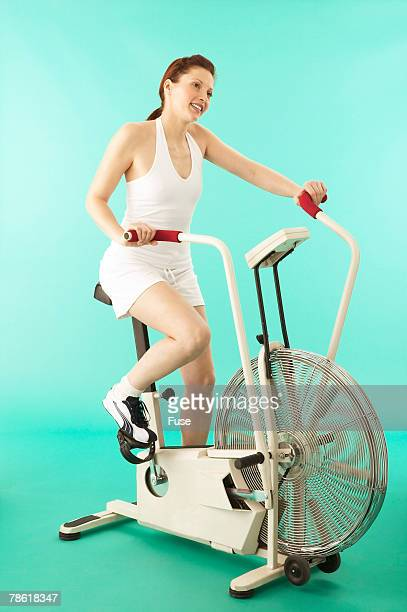 Young Woman Riding Exercise Bicycle