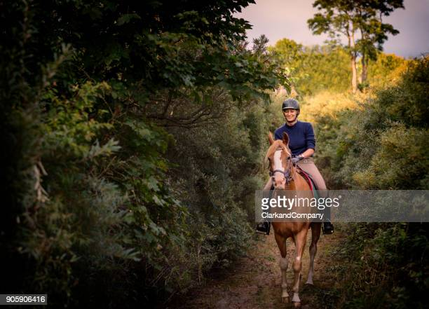 young woman riding her arabian horse through the woods - andare a cavallo foto e immagini stock