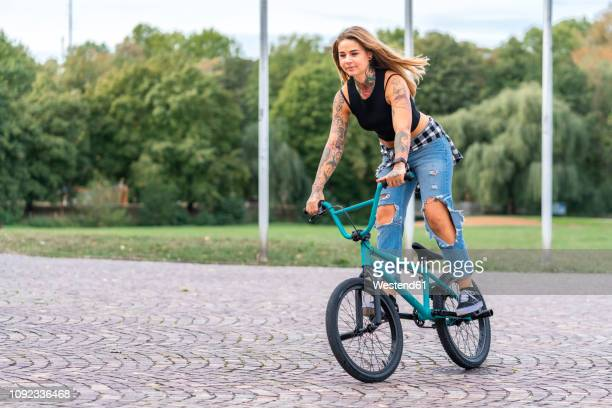 young woman riding her bmx bike - bmx cycling stock pictures, royalty-free photos & images