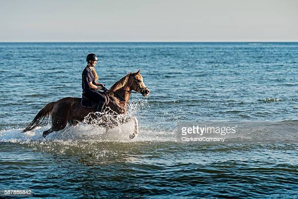 Young Woman Riding Her Horse on the Beach