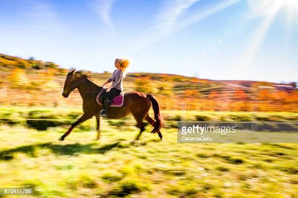 Junge Frau auf Pferd In Landschaft
