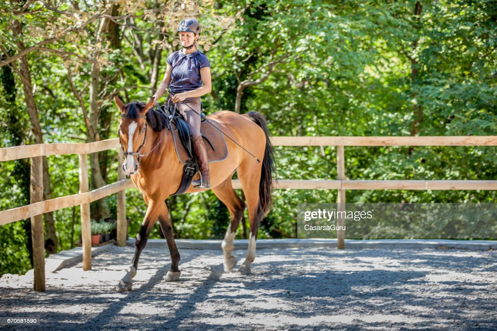 Young Woman Riding Horse in Manege : Stock Photo