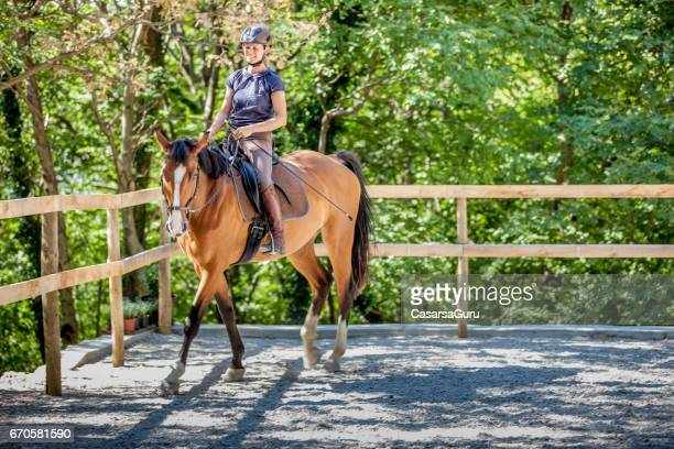 young woman riding horse in manege - dressage horse russia stock photos and pictures