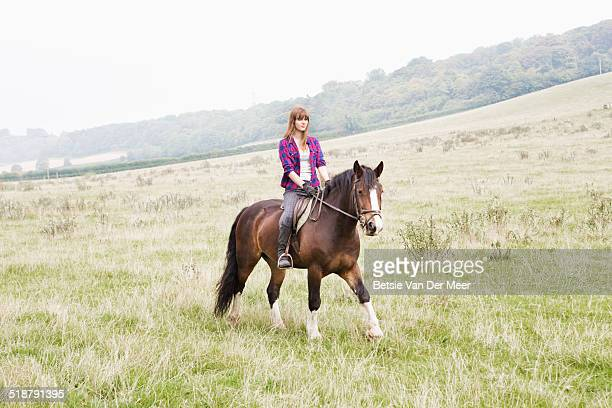 young woman riding horse through fields. - horse stock pictures, royalty-free photos & images