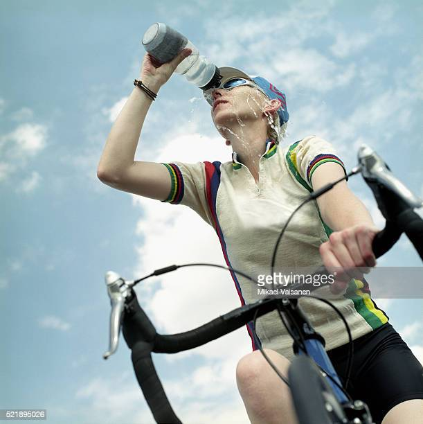 Young Woman Riding Mountain Bike and Drinking Water