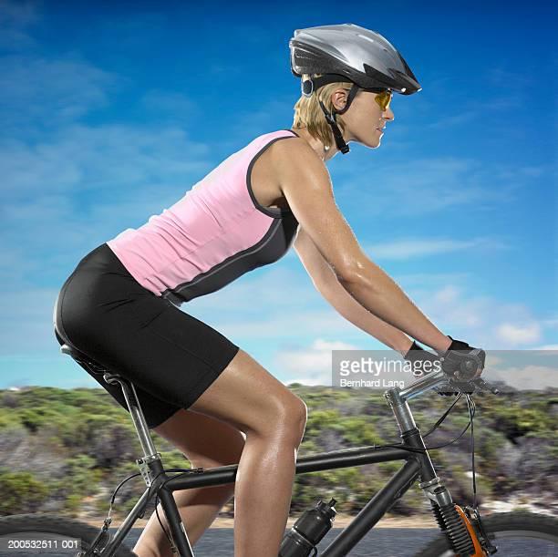 Young woman riding mountain bike, side view