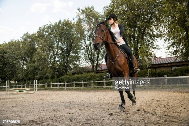 Young woman riding on horse