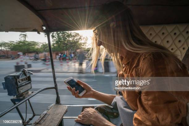 young woman riding on rickshaw in india text messaging on mobile phone, jaipur, india, southeast asia. people travel sharing communication concept - rickshaw stock pictures, royalty-free photos & images