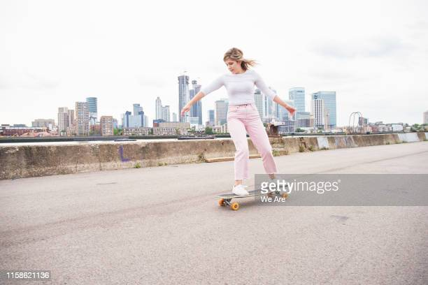 young woman riding on skateboard in city - skating stock pictures, royalty-free photos & images