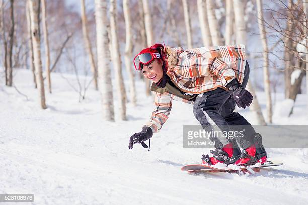 Young woman riding on snowboard in wintery landscape