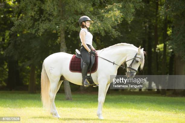 Young woman riding on white horse