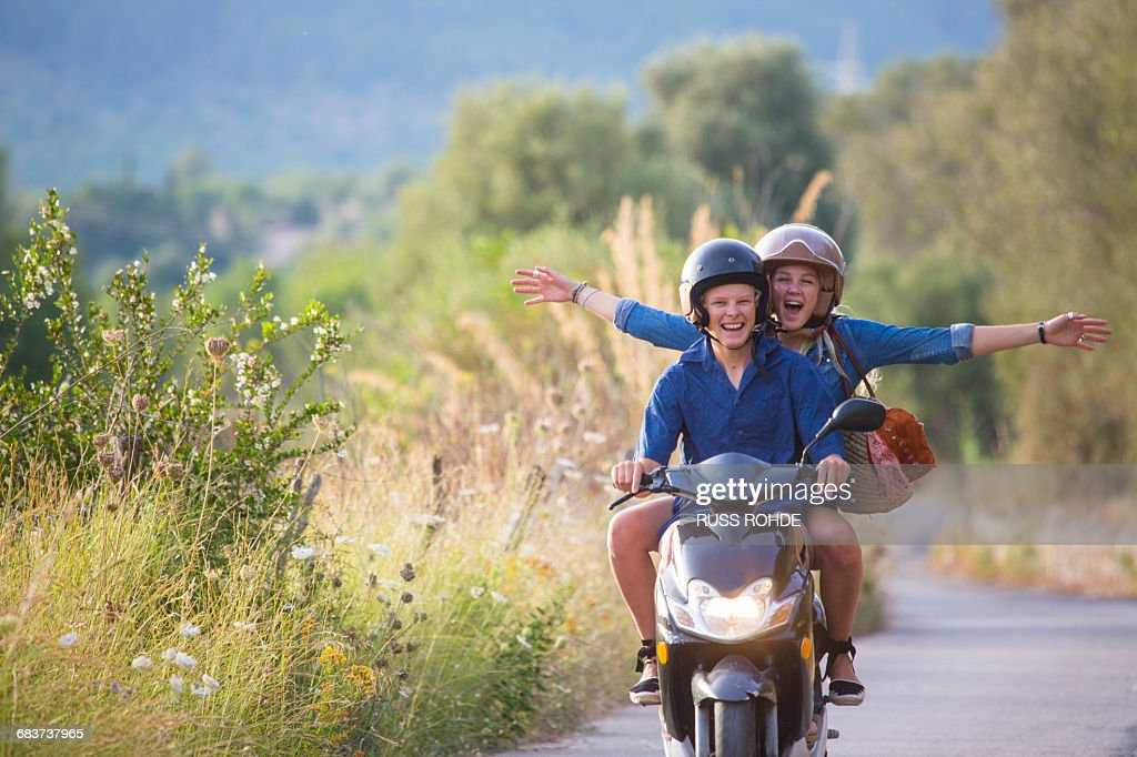 Young woman riding pillion on moped with arms open on rural road, Majorca, Spain : Stock Photo