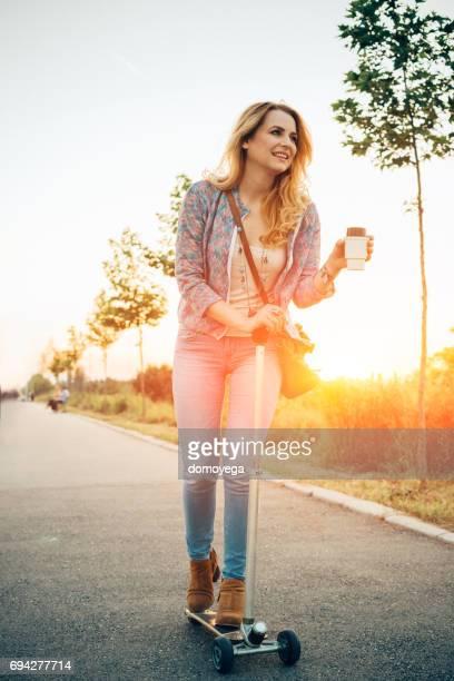 Jeune femme scooter pousser à cheval sur la piste cyclable et la réalisation de café