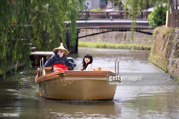 Young woman riding sightseeing boat with senior driver on Ono river