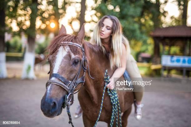Jeune femme équitation cheval caressant