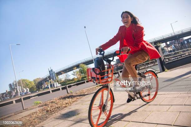 young woman riding through the city on a rental bike - lifestyles stock pictures, royalty-free photos & images