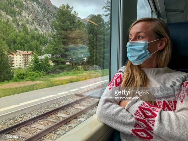 young woman riding train in switzerland wearing a medical mask during covid-19 pandemic - switzerland stock pictures, royalty-free photos & images