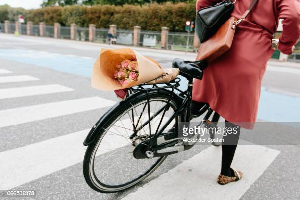 young woman riding with bouquet of flowers on the back of her bicycle - onherkenbaar persoon stockfoto's en -beelden
