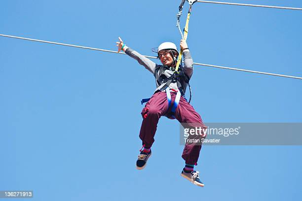Young woman riding zip-line