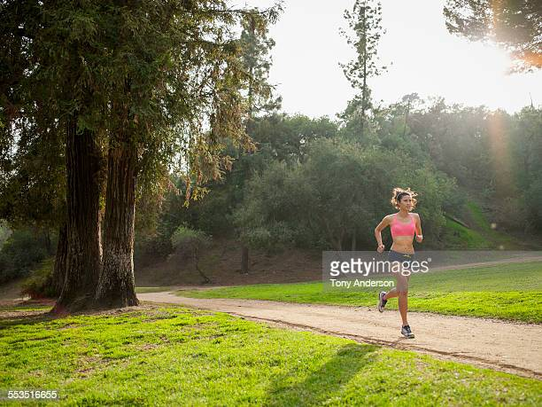 Young woman rinning along path outdoors