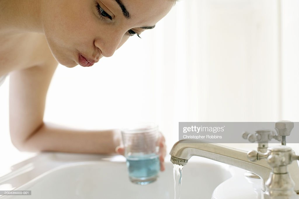 Young woman rinsing mouth, leaning over sink, close-up : Stock Photo