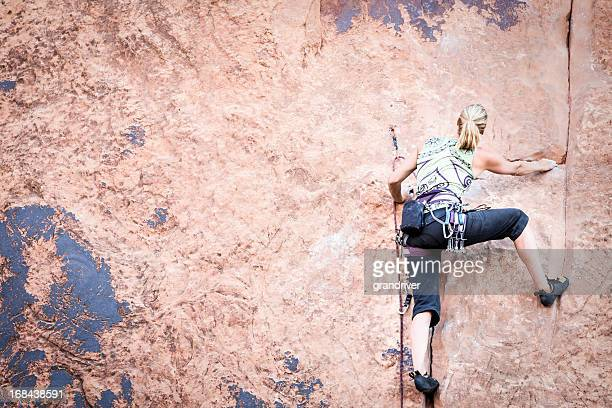 Young Woman Rock Climber on a sandstone cliff