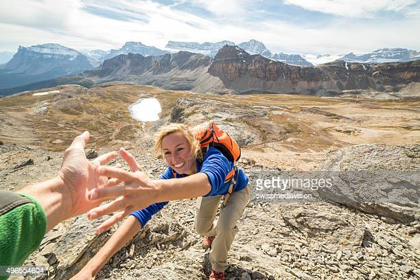 Young woman rock climbing, partner giving helping hand