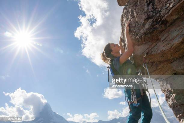 young woman rock climbs up mountain - pinnacle peak stock pictures, royalty-free photos & images