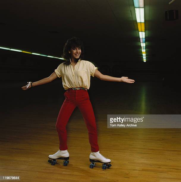 young woman roller skating on wooden floor, smiling, portrait - roller rink stock photos and pictures