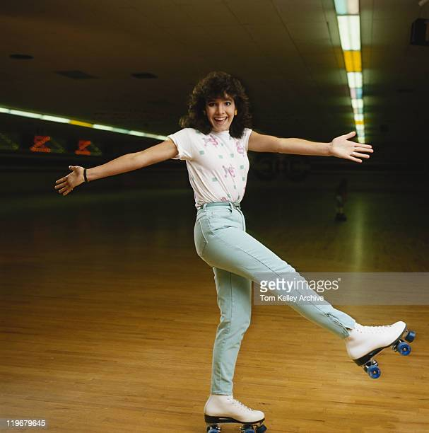 Young woman roller skating on wooden floor, smiling, portrait