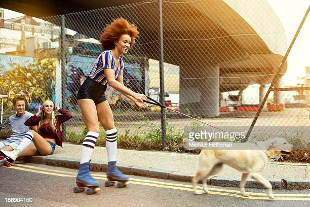 Young woman roller skating with dog