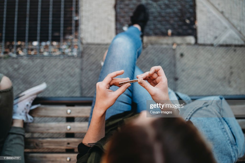 Young woman rolling cigarette sitting on the bench : Stock Photo