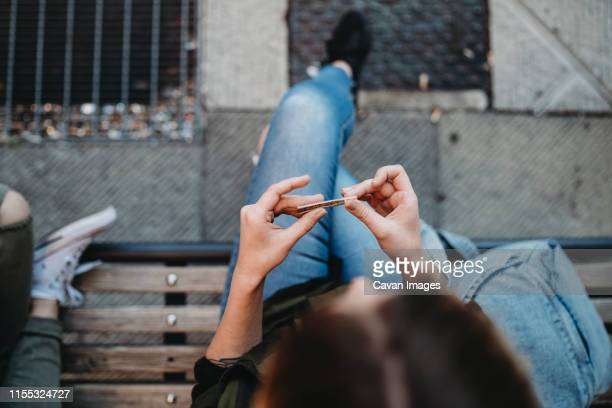 young woman rolling cigarette sitting on the bench - femme qui fume photos et images de collection