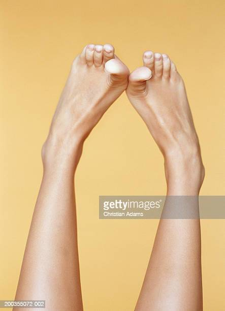 Young woman rubbing big toes together, close-up