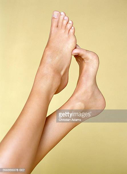 young woman rubbing bottom of foot with toes of other foot, close-up - piedi foto e immagini stock