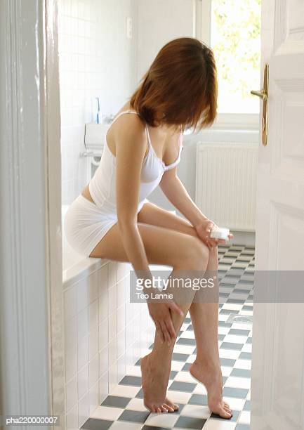 Young woman rubbing cream on legs.