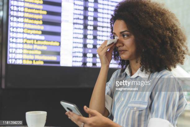 young woman rubbing her eyes with a tissue paper in the airport - conjuntivite imagens e fotografias de stock