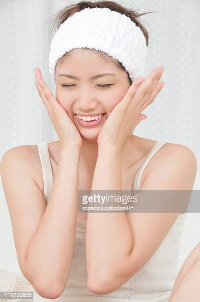 young woman rubbing her face - 頬 ストックフォトと画像