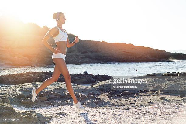 Young woman runing on the beach