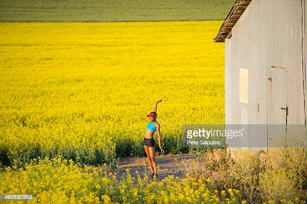 Young woman runner stretching in field of oil seed rape