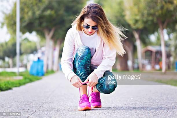 Junge Frau Läufer Schnürsenkel binden