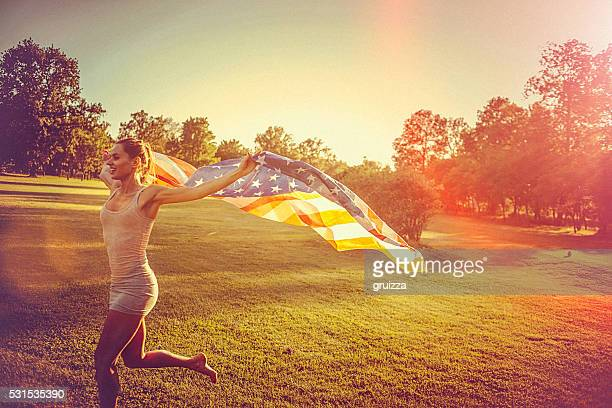 Young woman running across a meadow holding american flag