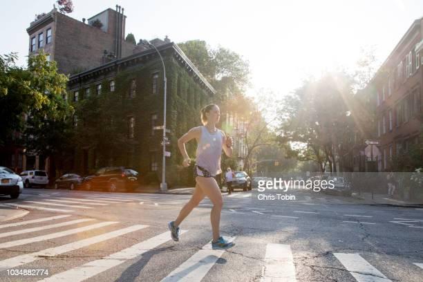 young woman running across crosswalk in city - トラック競技 ストックフォトと画像