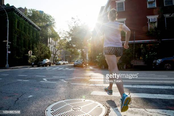 young woman running across crosswalk seen from behind - travessia de pedestres marca de rua - fotografias e filmes do acervo