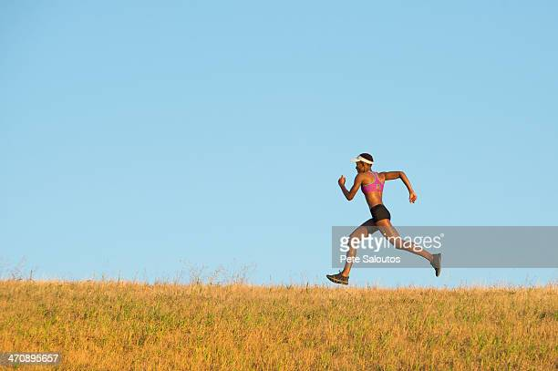 Young woman running across field