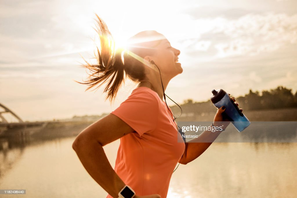 Young woman running against morning sun : Stock Photo