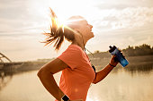 Young woman running against morning sun